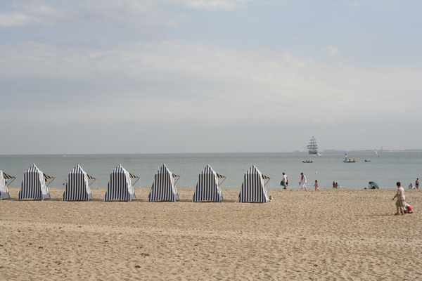 The beach of Royan. The old sailing ship on the horizon was a visitor of the Tour de France for sailing boats. How they get over the Alps is a mystery to me. (For Daphne: beach with blue-white striped tents)