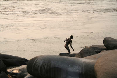 Young boy jumping into the Congo river